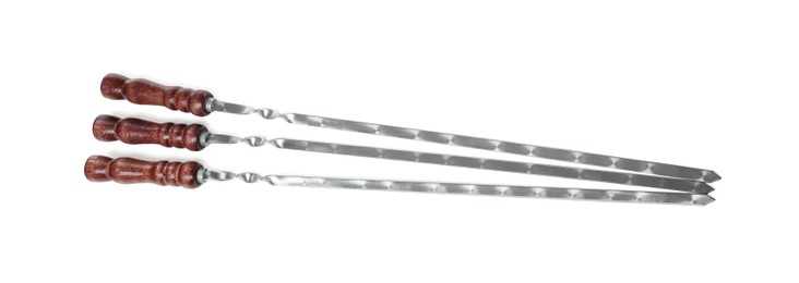 Metal skewers with wooden handle on white background, top view