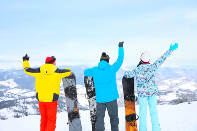 Friends with snowboards at mountain resort, back view. Winter vacation
