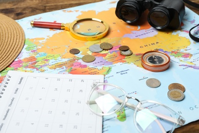 Different travel accessories and world map on table, closeup. Planning summer vacation trip