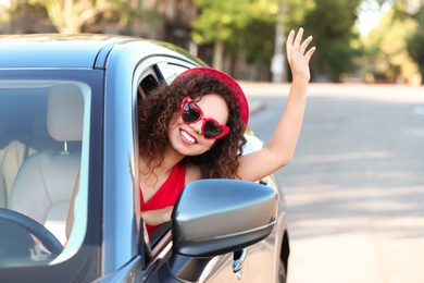 Young beautiful African-American woman wearing heart shaped glasses in car