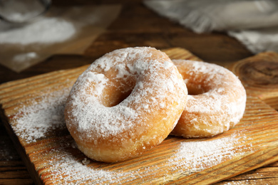 Delicious donuts with powdered sugar on wooden table