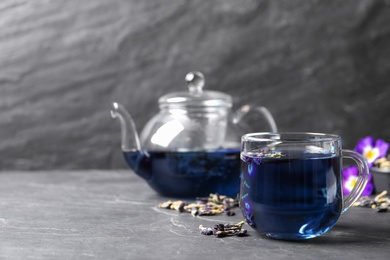 Glass cup of organic blue Anchan on black table, space for text. Herbal tea