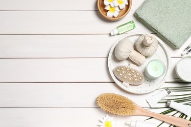 Flat lay composition with spa essentials on white wooden background. Space for text