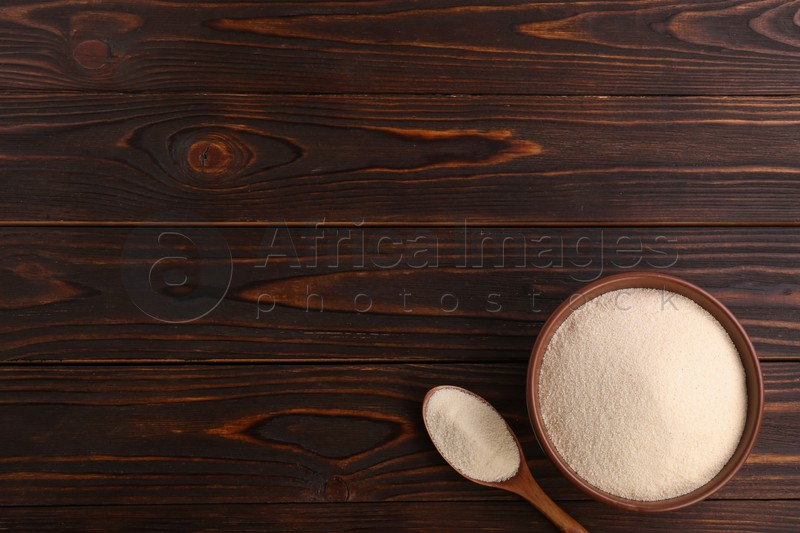 Uncooked organic semolina on wooden table, flat lay. Space for text
