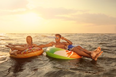 Happy couple with inflatable rings in sea