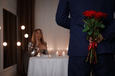 Man hiding roses for his beloved woman in restaurant at romantic dinner