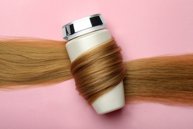 Bottle wrapped in lock of hair on pink background, top view. Natural cosmetic product