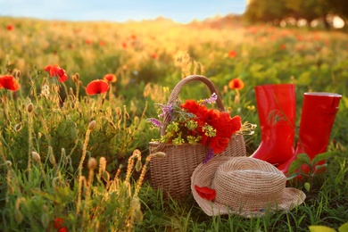 Basket of wildflowers with straw hat and boots in sunlit poppy field