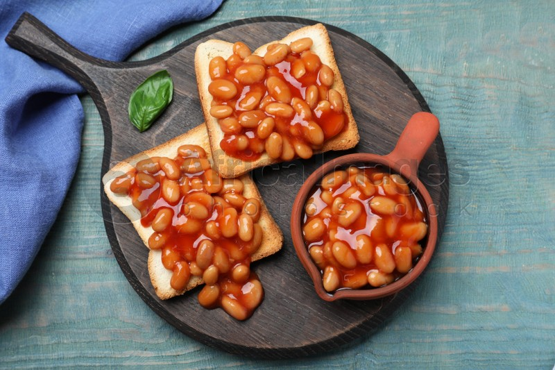 Toasts with delicious canned beans on light blue wooden table, top view