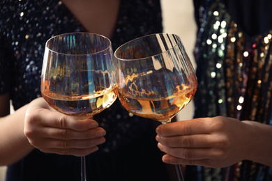 Women clinking glasses with white wine, closeup