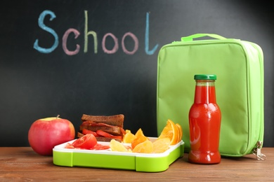 Appetizing food in lunch box and bag on table near chalkboard with word SCHOOL