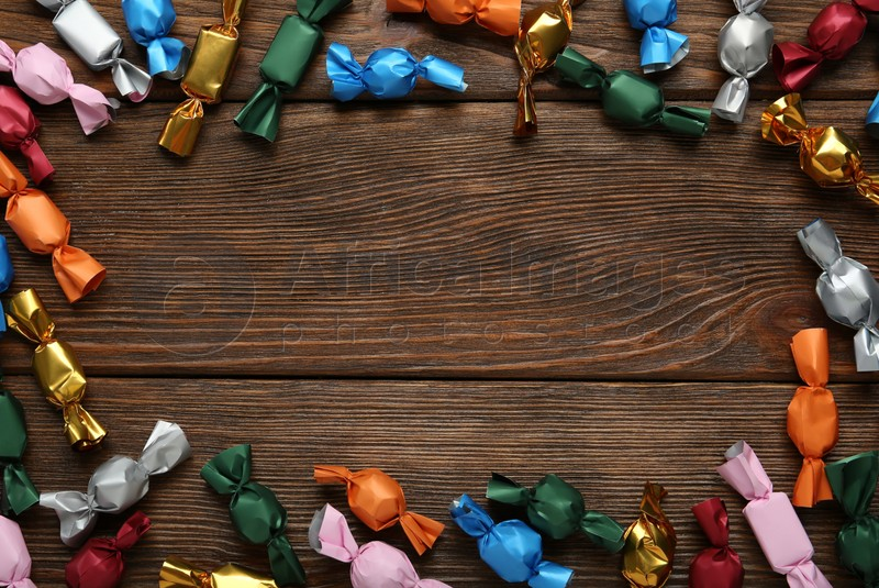 Frame of candies in colorful wrappers on wooden table, flat lay. Space for text