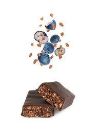 Tasty chocolate glazed protein bars and granola with blueberries falling on white background