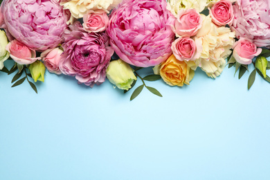 Flat lay composition with beautiful flowers and space for text on light blue background. Floral card design