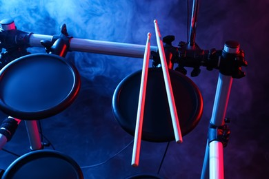 Modern electronic drum kit with sticks on dark background, color toned. Musical instrument