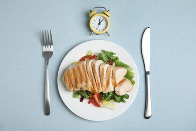 Plate of appetizing food, alarm clock and cutlery on light blue table, flat lay. Nutrition regime