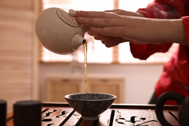 Master pouring freshly brewed tea into cup during traditional ceremony at table, closeup
