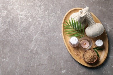 Tray of spa items on grey table, top view. Space for text