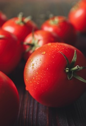 Fresh ripe tomatoes on wooden table, closeup
