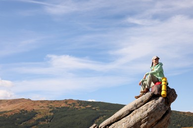 Young woman with backpack and sleeping mat on cliff in mountains. Space for text