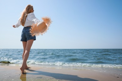 Young woman with straw hat near sea on sunny day in summer, low angle view