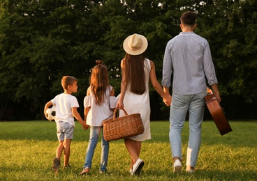 Happy family with picnic basket in park