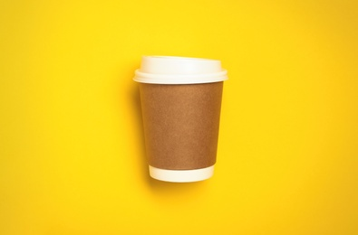 Takeaway paper coffee cup on yellow background, top view