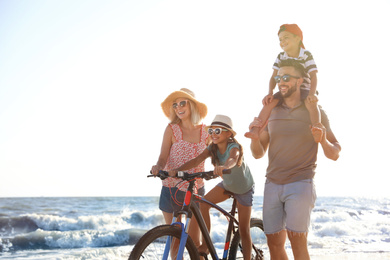 Happy family with bicycle on beach near sea