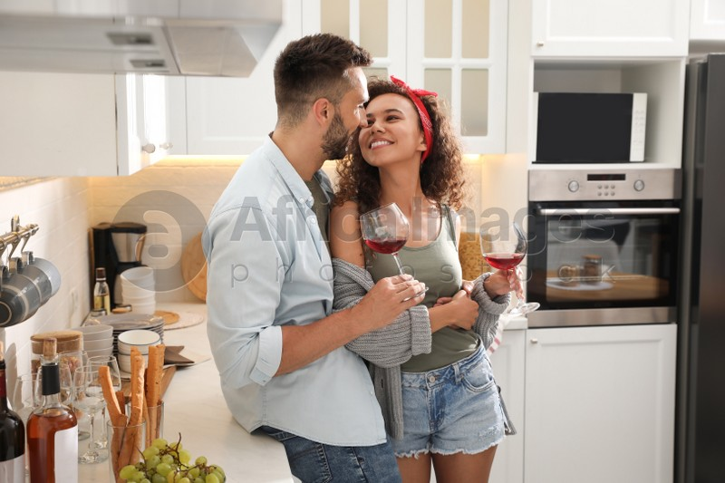 Lovely couple with glasses of wine enjoying time together during romantic dinner in kitchen