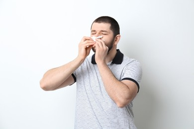 Man with tissue suffering from runny nose on white background