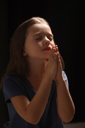 Cute little girl with hands clasped together praying on black background