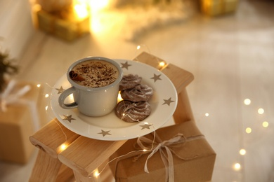Tasty hot drink, chocolate cookies and Christmas lights indoors. Space for text