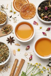 Flat lay composition with fresh brewed tea and dry leaves on white wooden table