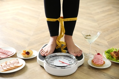 Food, alcohol left after holidays and woman with measuring tape standing on scales indoors, closeup. Overweight problem