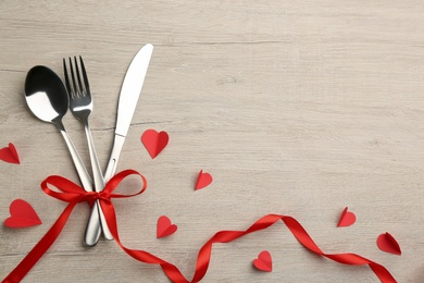 Cutlery set and red ribbon on background, flat lay with space for text. Valentine's Day dinner