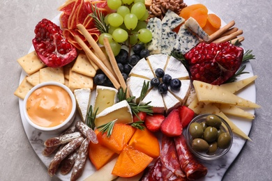 Assorted appetizers served on light grey table, view from above