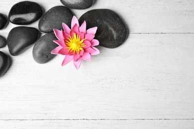 Stones with lotus flower and space for text on white wooden background, flat lay. Zen lifestyle