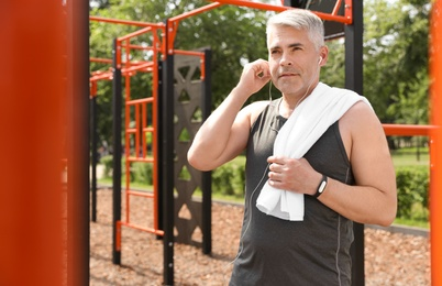 Handsome mature man listening to music on sports ground, space for text. Healthy lifestyle