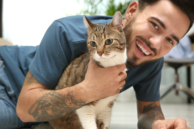 Happy man with cat on floor at home. Friendly pet