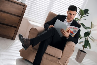Man reading culinary magazine in armchair at home