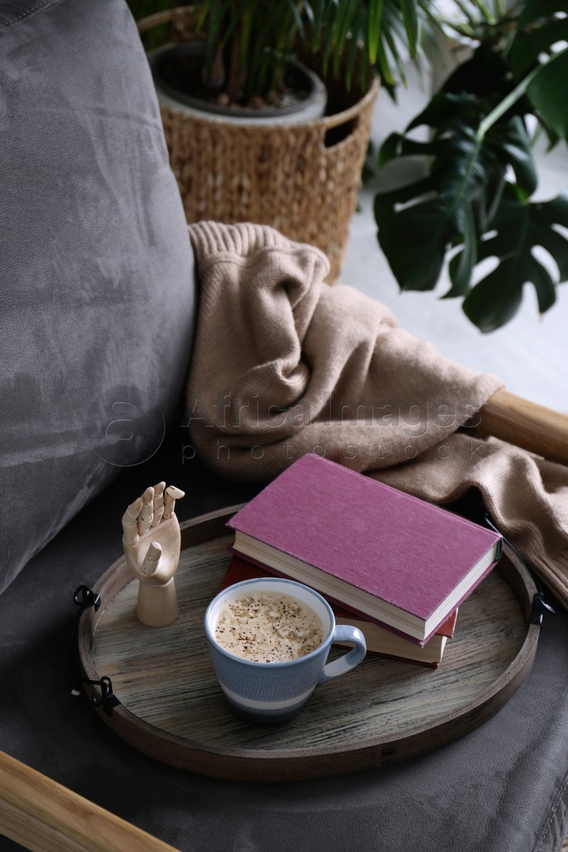 Wooden tray with books and coffee on armchair indoors