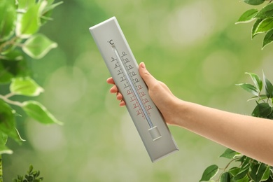 Woman with weather thermometer on blurred background, closeup
