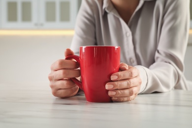 Woman with red cup at table indoors, closeup