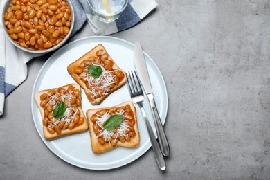 Toasts with delicious canned beans on light grey table, flat lay. Space for text