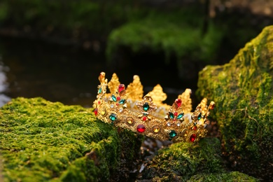 Beautiful golden crown on stones with green moss outdoors. Fantasy item