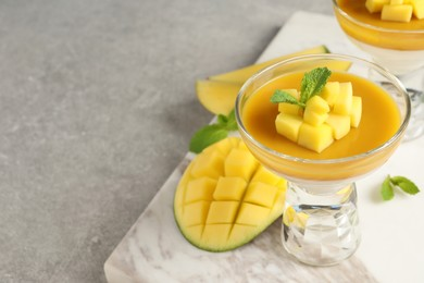 Delicious panna cotta with mango coulis and fresh fruit pieces on light grey table. Space for text