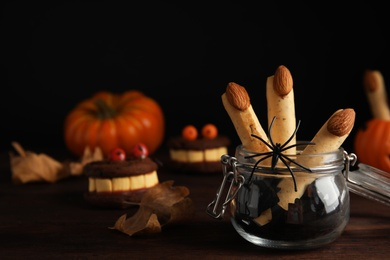 Delicious desserts decorated as monster fingers on wooden table. Halloween treat