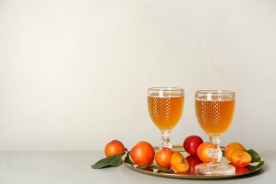 Delicious plum liquor and ripe fruits on light table. Homemade strong alcoholic beverage