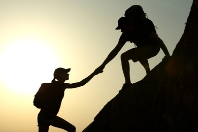Silhouettes of man and woman helping each other to climb on hill against sunset