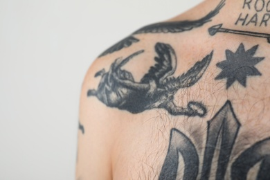 Young man with tattoos on body against white background, closeup